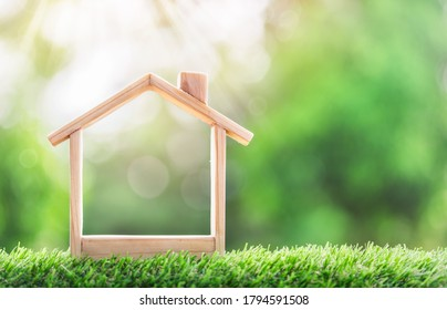 Wooden model house place on the grass. concept of real estate investment. planning savings money of coins to buy a home concept for property, mortgage and real estate investment, savings for a house.