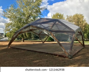 Wooden modular building in the form of a dome. The tent stands on the sand in the center of the city park.