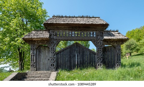 Wooden monastery access gate with medieval sculptures on the polls in the forest, surrounded by green grass with blue sky in the background