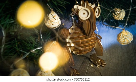 Wooden monster craftwork made of plywood on the background of a Christmas tree