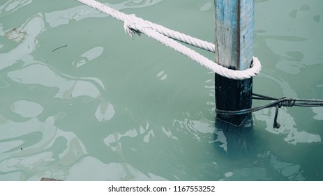 Wooden mooring post in lake /sea /water with mooring rope where boats can be stopped and tied up.