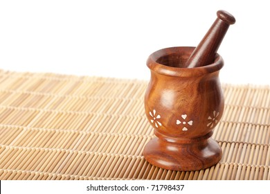 Wooden mortar with pestle on bamboo mat