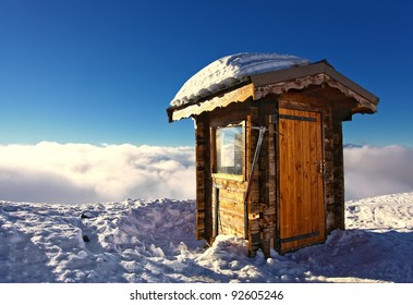 Wooden Mountain Hut Above Clouds in French Alps on snowy mountain cliff with blue sky and sun for Ski Patrol