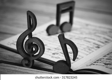 Wooden music notes and a vintage sheet music from 19th century on a wooden desk.