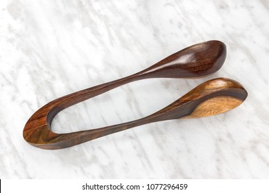 Wooden musical spoons, folk percussion instrument on marble background.