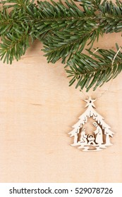 Wooden Nativity scene hanged on branch of fir. Empty space for text