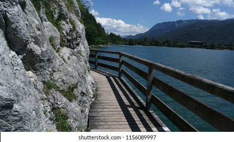 Wooden natural trail good for walking and jogging and a view of the beautiful lake Wolfgangsee in Austria.