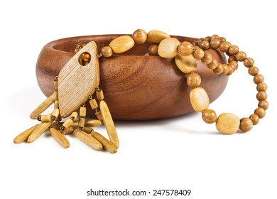 Wooden necklace in a wooden bowl on a white background