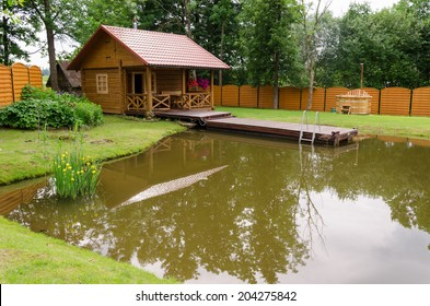 wooden new rural bathhouse and pond with floating plank footbridge in garden