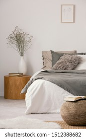 Wooden nightstand table next to king size bed with white and grey bedding in simple bedroom interior