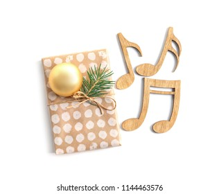 Wooden notes and gift box on white background. Christmas music concept
