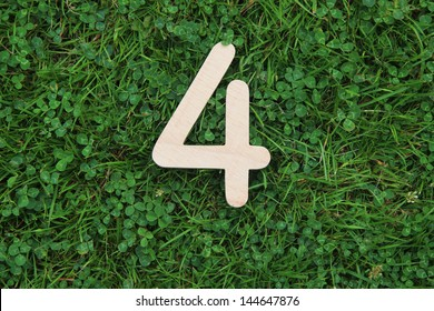 wooden number 4 on grass and clover background