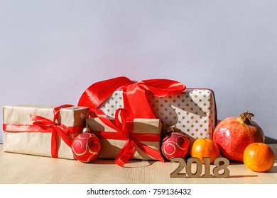 Wooden numbers 2018, fruits and gift boxes lie on the background.