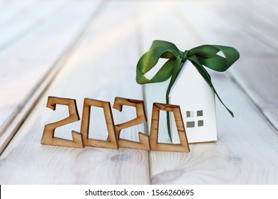 wooden numbers form the number 2020 and a paper house with a green ribbon. individual real estate is a good gift