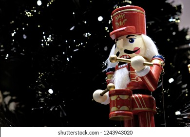 Wooden nutcracker with drum near a Christmas tree