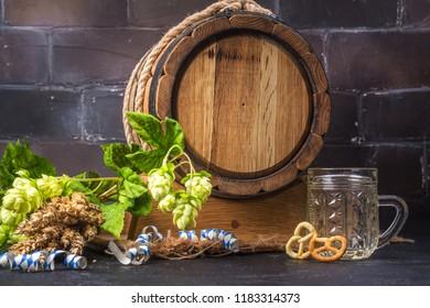 Wooden oak barrel, hops branches, wheat ears on dark background. Oktoberfest background. Copy space