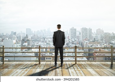 Wooden observation platform with foggy city view and businessman