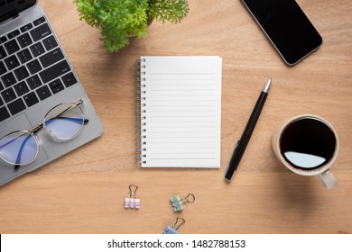 Wooden office desk table with blank notebook, laptop computer, cup of black coffee and supplies. Top view with copy space, flat lay.
