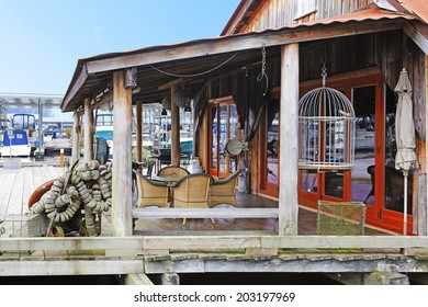 Wooden old building with wicker table set. View of boats behind it. Gig Harbor.
