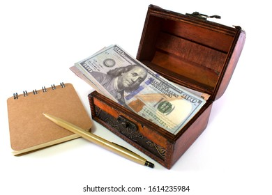 Wooden old casket with notepad and dollars, business theme.Isolated on a white background.