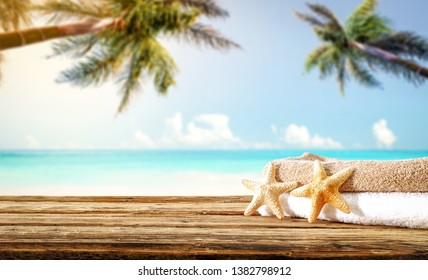 Wooden old desk of free space for your decoration. Summer towel and landscape of beach with palms. Summer suny day.