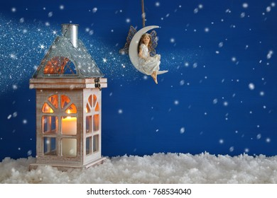 Wooden old house with candle and fairy on the moon over the snow and blue background