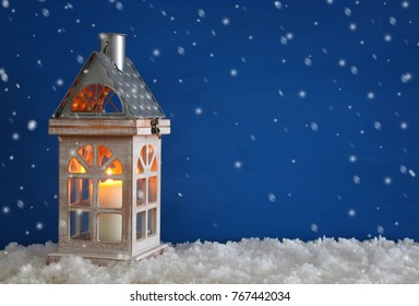 Wooden old house with candle over the snow and blue background