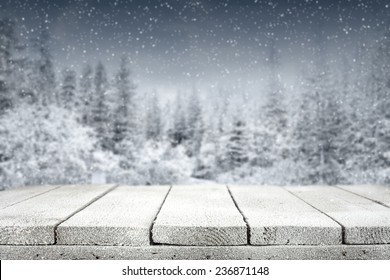 wooden old table with frost and forest on background