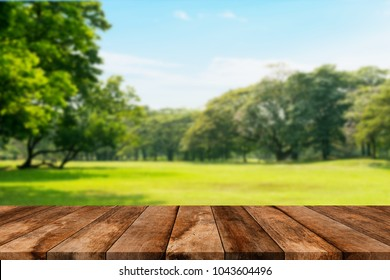 Wooden old table isolated on blurred green nature background. For your product placement or montage with focus to the table top in the foreground. Empty wooden brown shelf. shelves