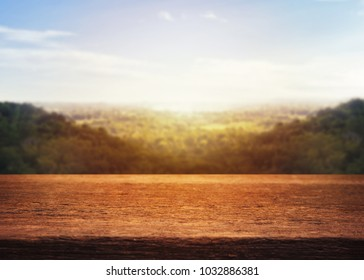 Wooden old table on mountain and cloud sky background in the morning. For your product placement or montage with focus to the table top in the foreground. Empty wooden dark shelf. shelves