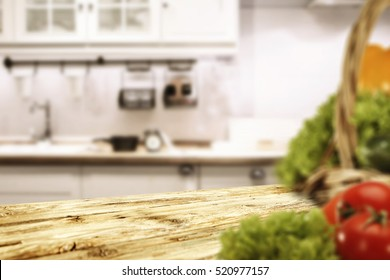 Wooden old table place and kitchen interior with blurred vegetables on top