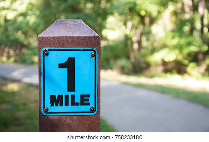 A wooden one mile marker post along a cement running path.  Shallow depth of field so background is out of focus.