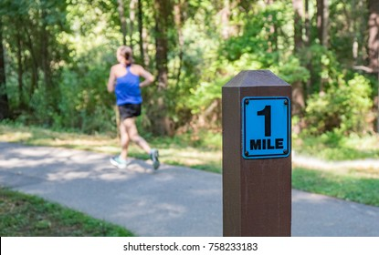 A wooden one mile marker post in the foreground with a woman running in the background on a cement pathway.  Shallow depth of field so the background is out of focus.