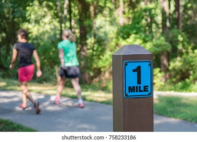 A wooden one mile marker post in the foreground with two women walking in the background on a cement path.  Shallow depth of field so background is out of focus.