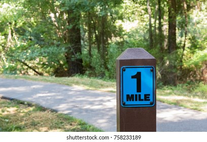 Wooden one mile marker post along a cement running path.