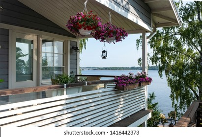 Wooden, open terrace decorated with flowers. Summer landscape, view of the bay. Finnish cottages.