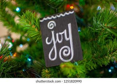 A wooden ornament with the word 'Joy' Hangs on a light christmas