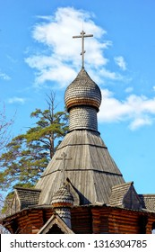 Wooden Orthodox church, dome with a cross and blue sky.
