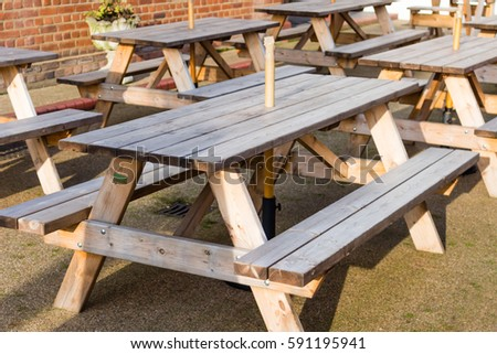 Wooden Outdoor Tables With Benches Attached And A Place To Put An Umbrella  In The Middle