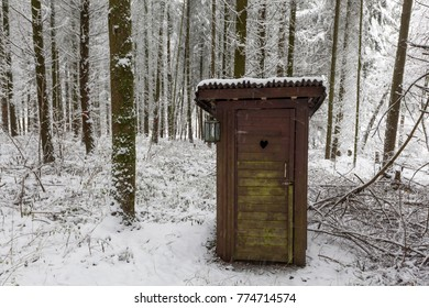 Wooden outdoor toilet in a snowy winter forest