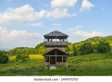 Wooden outpost built in medieval style on the green hill. Observation tower watching over the hills and valley near Horezu, Romania.