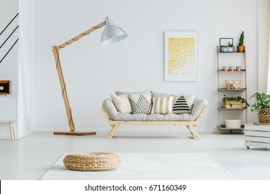 Wooden oversize lamp standing in a room next to sofa