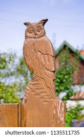 Wooden owl statue on the fence
