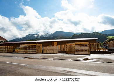 Wooden packing pallets stacked ready for use outside a depot alongside a tarred road with mountain backdrop