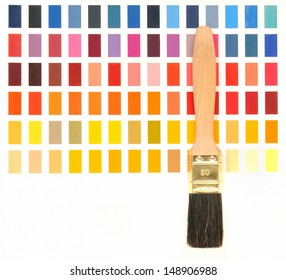 Wooden paint brush in front of a color chart