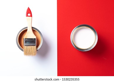 Wooden paint brush, open paint cans on trendy red and white background. Top view, copy space. Appartment renovation, repair, building and home design concept