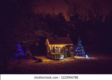 Wooden painted yellow private children`s play house in home garden, decorated with Christmas LED string lights outdoors in cold winder night. Decorated Christmas fir tree.