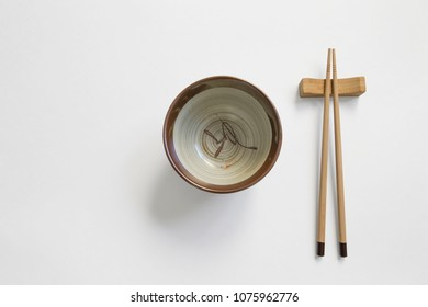 Wooden pairs of chopsticks and ceramic dish (plate) on white background. space for text, image, advertisement. cooking culture in Asian countries.