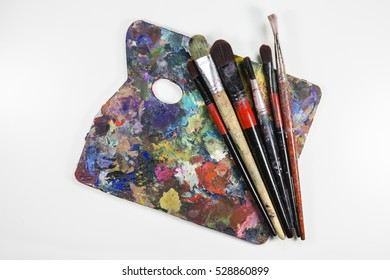 Wooden Palette with Blobs of Paint and Brushes on White Background. Top view.