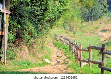 "Wooden palisade along nature trail  with hiking directions in natural environment. Selective focus. ""Maddalena"" (Magdalene) is the name of a mountain in Brescia, Italy."